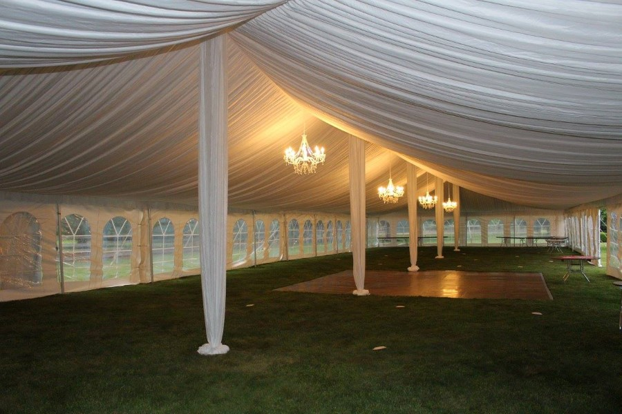 Chandelier Lighting in a 40x120 Pole Tent with Fabric Ceiling Liner and Center pole Drapes